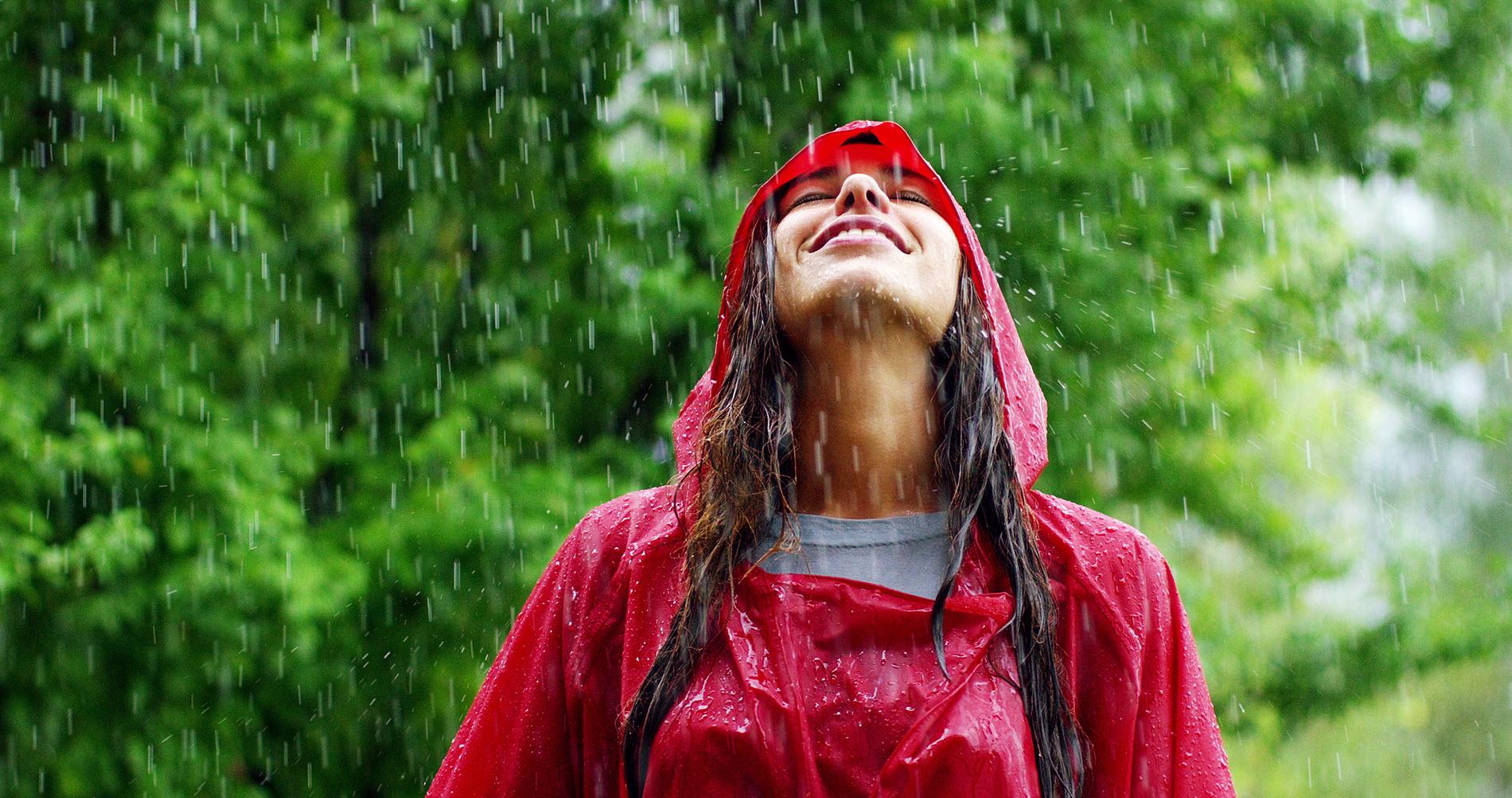 Vrouw met rood regenpak in regen